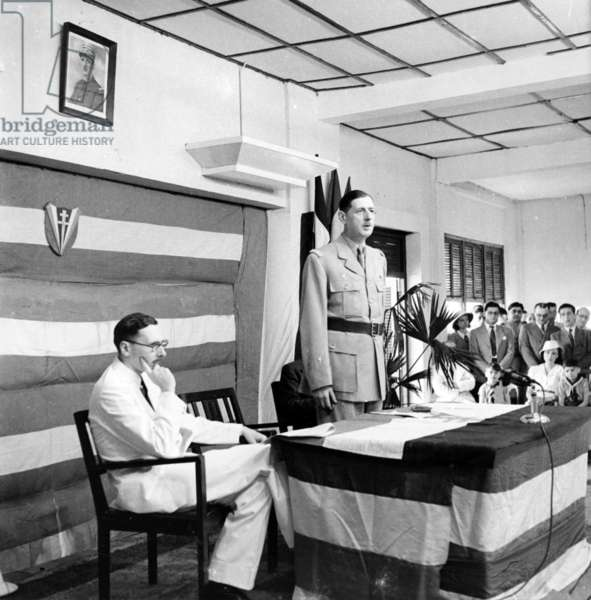 General de Gaulle giving a speech at a conference in Brazzaville, with René Pleven seated to his left, 27-28 January 1944 (b/w photo)
