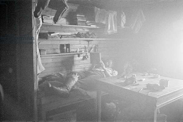 Paul-Emile Victor in the common house, to him and his three companions, Ammassalik, Greenland, 1935 (b/w photo)