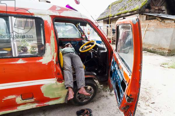 Man sleeping in a van, Dokan, North Sumatra, Indonesia (photo)