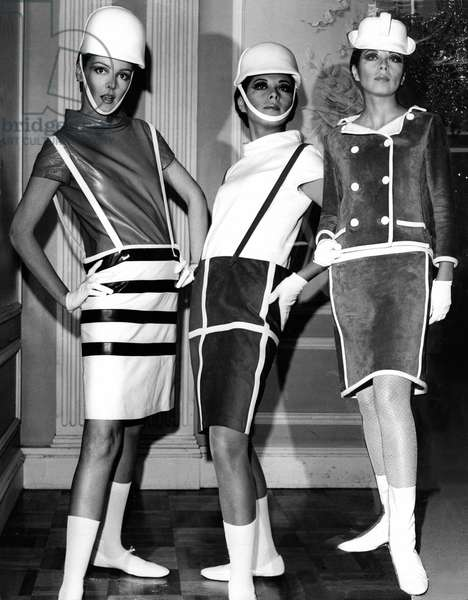 Leather barrel-shaped skirts with suspenders and cowl necked blouses designed by Andre Courreges, 1965