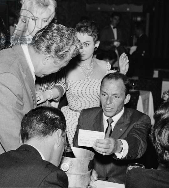 Frank Sinatra with Producer Harry Saltzman, showgirls and journalist, Pigalle 195, London, UK, 1955 (b/w photo)
