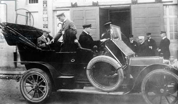 Edward, Prince of Wales, (L) seated in a 1910 Pierce-Arrow touring car at the Zeppelin works at Friedrichschafen, Germany. Ferdinand Graf von Zeppelin is in white cap near the door. 3/31/1913