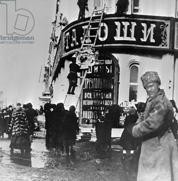 Residents of Tomsk hurling down tsarist emblems from signboards, 8th March, 1917 (b/w photo)