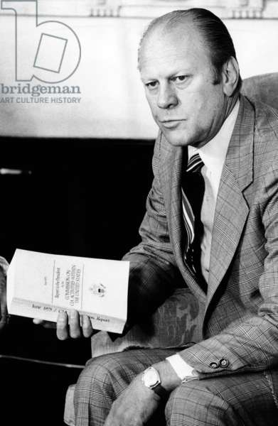 President Gerald Ford holds the Official Report of the Rockefeller Commission's investigation of the CIA, June 6, 1975