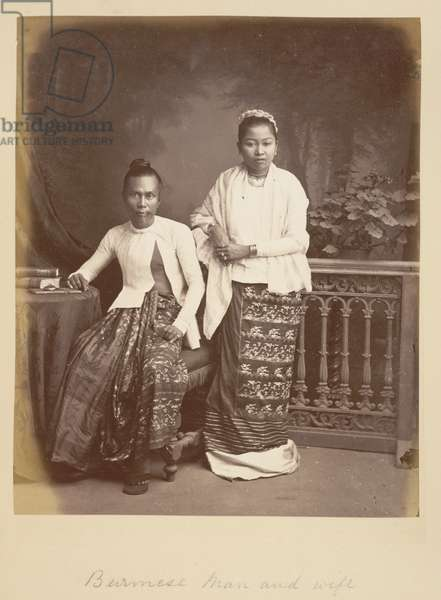 [Portrait of a] Burmese man and wife. Photograph of a Burmese man and woman in Burma (Myanmar) in the 1880s. In this posed studio portrait, they wear traditional Burmese dress, including the wrap-around skirt known as hta-mein worn by women and a more voluminous version for men known as a pahso