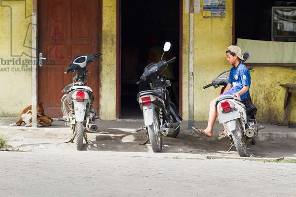 Parked motorcycles and boy, Dokan, North Sumatra, Indonesia (photo)