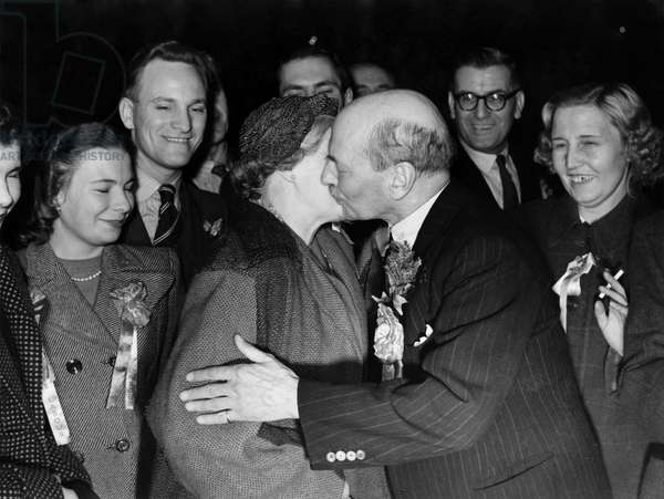 A kiss for Clement Attlee from his wife after his ardious election campaign, but pleased with his personal success in the polls as West Walthamstow, London.