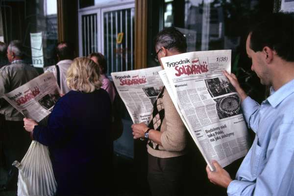 Warsaw, Poland, June 1989 People read oppostion newspaper Tygodnik Solidarnosc, While standing in a queue at a kiosk. Election campaign, Constitution Square.