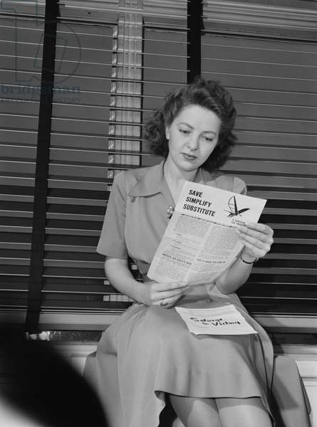 Woman Reading Government Literature Regarding Rationing and Salvaging during World War II, 1942 (b/w photo)