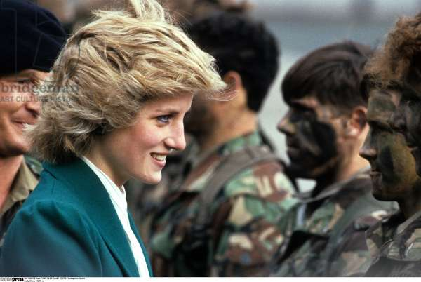 Lady Diana Princess of Wales 10/85 rud wife Princess England UK nobility wife of Prince Charles of Wales blond serious Blazer green outdoors soldier receiving standing half crosswise smiling