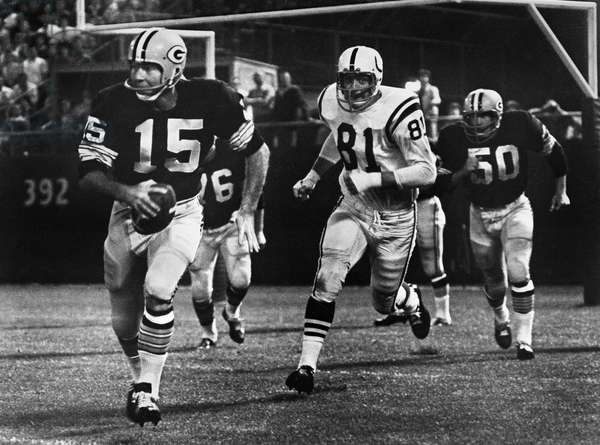 FOOTBALL GAME, 1966 Quarterback Bart Starr of the Green Bay Packers attempting to run for a first down against the Baltimore Colts after failing to find an open receiver, during a game at County Stadium, Milwaukee, Wisconsin, 10 September 1966.