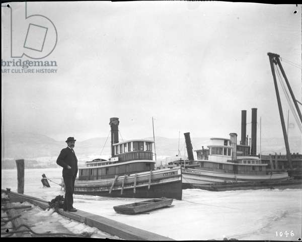 Man on pier near several tugboats in icy water, 1895 (b/w photo)
