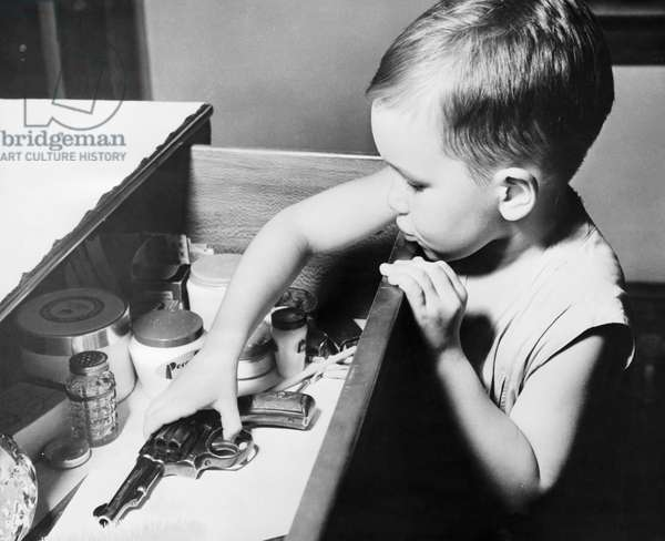 Boy picking up a revolver from a drawer