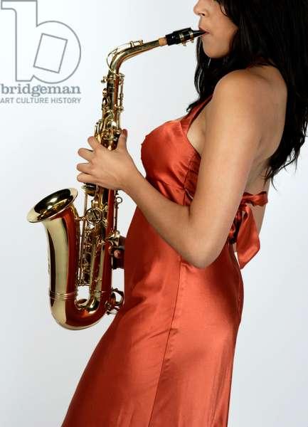 Female musician  playing an alto saxophone