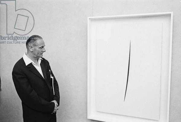 A man observing a Concetto Spaziale by Lucio Fontana at the 32nd Art Biennale, Venezia, Italy