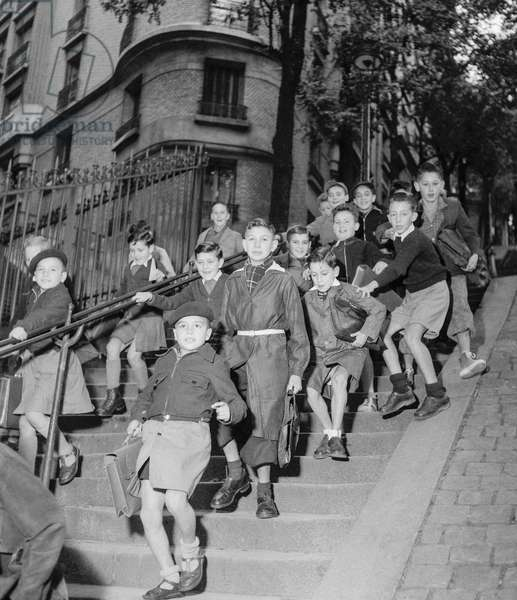 The start of the new school year in Paris on October 2, 1950 : schoolboys in Montmartre on the way of the school (b/w photo)