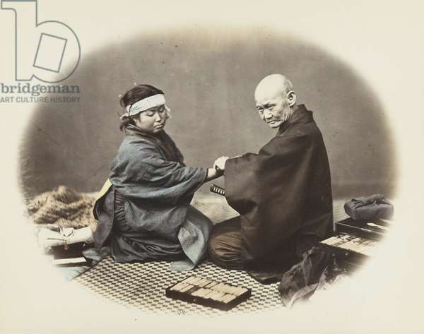 Japanese man and woman in traditional dress (hand-coloured b/w photo)