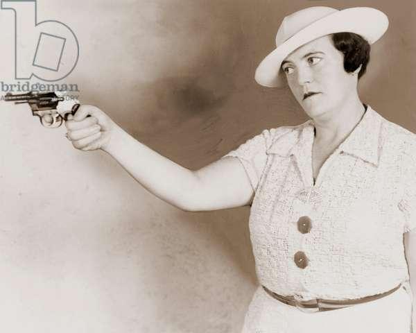 Serious Woman Aiming a Revolver, 1937 (silver print photograph)