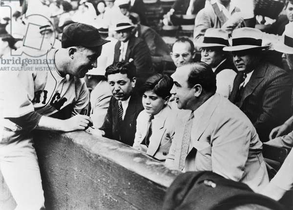 AL CAPONE (1899-1947) American gangster. At a Chicago Cubs game with his son, Sonny Capone; Cubs catcher Gabby Hartnett is autographing a ball for Sonny. Photograph, 1931.