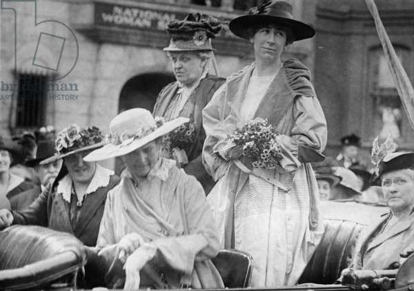 Jeannette Rankin (1880-1973), first woman member of the U.S. Congress stands in an open car in front of the Washington D.C. headquarters of the National Woman's Suffrage Association. To Rankin's right is veteran woman's rights advocate Carrie Catt