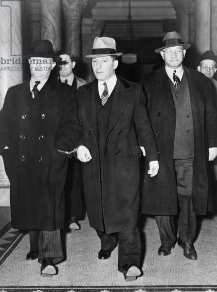 LOUIS 'LEPKE' BUCHALTER (1897-1944). American mobster and head of the hit squad Murder Inc. Pictured at center handcuffed to F.B.I. Director J. Edgar Hoover, entering a courthouse, 1940.