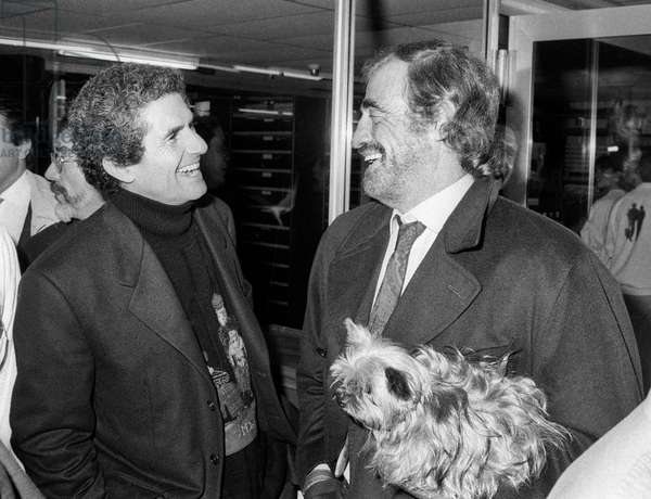 French director Claude Lelouch and Actor Jean Paul Belmondo (with his yorkshire) arriving at the video cassettes factory