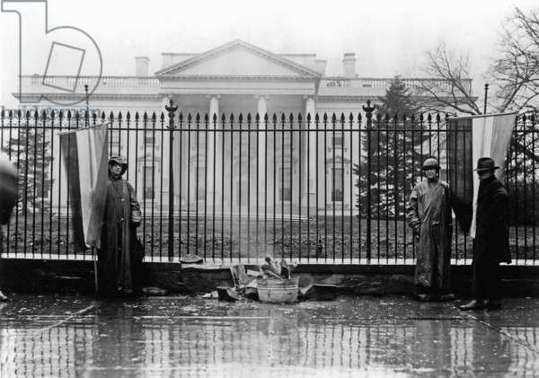 Suffrage pickets tend their watchfire during a protest in front of the White House, 1919 (b/w photo)