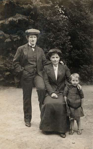 Two women, one dressed as man, with female child (b/w photo)