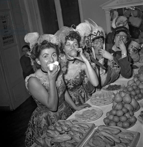 The dressmaker's apprentices celebrating the Saint Catherine at Maud et Nano's, Paris, November 14, 1949, here eating bread and fruits (b/w photo)