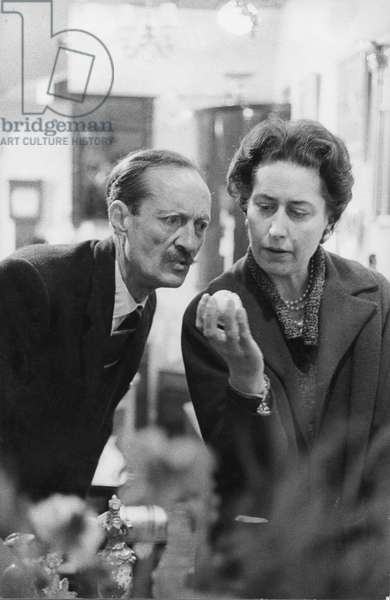 Lady and gent looking at a ball (b/w photo)