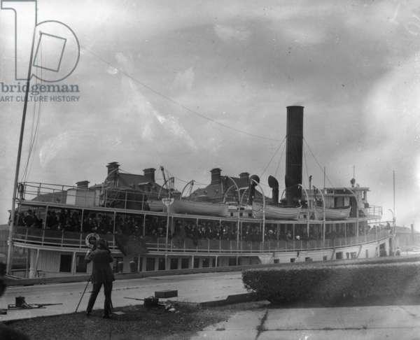 ELLIS ISLAND, c.1910 A ship full of immigrants arriving at Ellis Island. Photograph, c.1910.