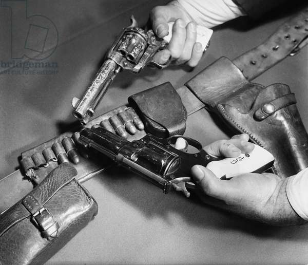 Close-up of man's hands holding a .45 Caliber Colt Army Revolver with a Smith and Wesson .357 Magnum Revolver