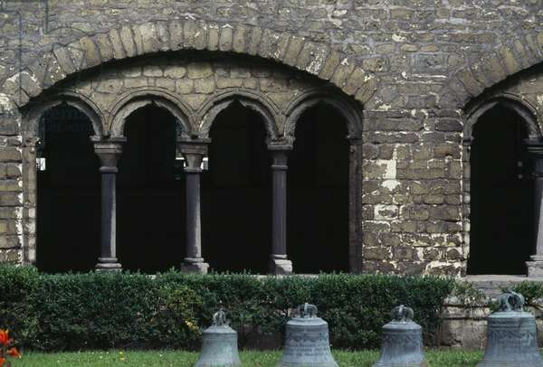 Bronze bells on lawn in cloister of Collegiate church of St Gertrude, Nivelles, Belgium, 11th century