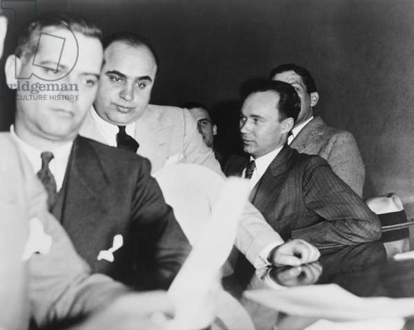 Al Capone, at the time of his indictment for tax evasion, June 5, 1931. At right is one of Capone's attorneys, Michael Ahern.