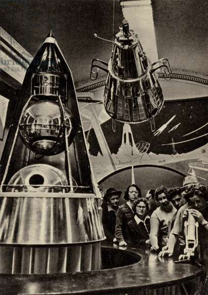 Group of tourists looking at a replica of the Soviet Sputnik satellite in the Exhibition of Achievements of the National Economy in Moscow, USSR, 1960s (b/w photo)