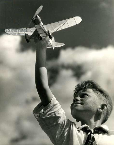 Boy holding up a model airplane, New York, USA, 1932 (gelatin silver photo)