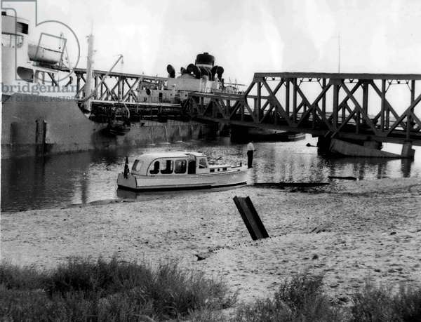 """Jan. 01, 1955 - TANKER"""" WORLD PEACE"""" WRECKS RAILWAY BRIDGE OVER THE SUEZ CANAL... The Liberian Tanker"""" WORLD PEACE"""" crashed into the railway bridge which crosses the Suez Canal - at EL FERDAN blocking the canal for many miles.. Owners of ships approaching the Canal were requested to slow thear vessels up to ease conapetion until the -ray was cleared. KEYSTONE PHOTO SHOWS: - The scene after the tanker had crashed into the bridge - at El Ferdan"""