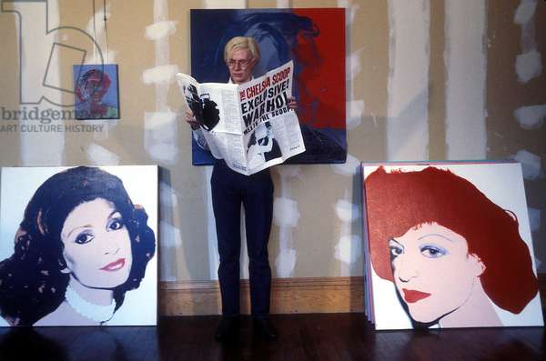 Portrait of American artist Andy Warhol reading a newspaper surrounds his works on 22/07/1978 (photo)