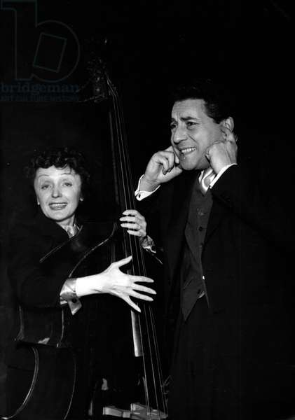 """Jan. 01, 1955 - Not So Loud, Edith! : Jacques Pilis, famous singer, and his famous wife, Edith Piaf, seem to have an argument. Jacques finds Edith"""" Sings Tco Loud"""" but Edith still goes on. This Amusing picture was taken during a rehearsal at the Olympia, Paris, last night. The couple will appear at the Olympia in a program of new songs"""