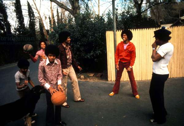 Portrait of members of the Jackson Five (Jackie, Tito, Jermaine, Marlon, and Michael) playing basketball 1973