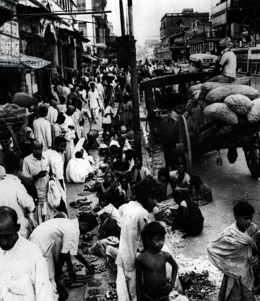 Jan. 01, 1955 - Wholesale retailing in Kolkata: Calcutta today is largely a city of congestion and overcrowding but nowhere so conspicuously as in Bowbazar. This picture shows the street during a comparatively quiet time of the day with vegetable retailers selling their goods on the pavement outside the big wholesale vegetable market near Sealdah Railway Station. In the evening, when thousands of office workers make their way to the station on their way home - the pavement becomes almost impassable