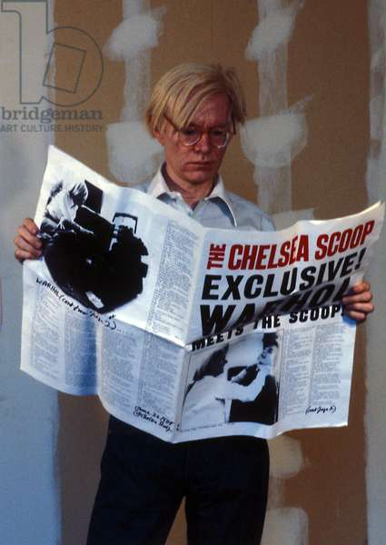 American artist Andy Warhol reading a newspaper talking about him in 1978 (photo)