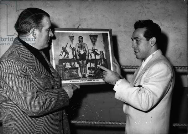 Jan. 01, 1955 - Paddi Di Marco Sees plants Des Sports Training Quarters: Paddi De Marco the famous American Boxer, ex-World's light weight Champ, looks at a Portrait of Marcel Gerdan (French Boxer killed in an air crash) while visiting the Palais Des sports training Quarters in Paris, this afternoon.Paddi has several European bouts on the Program me