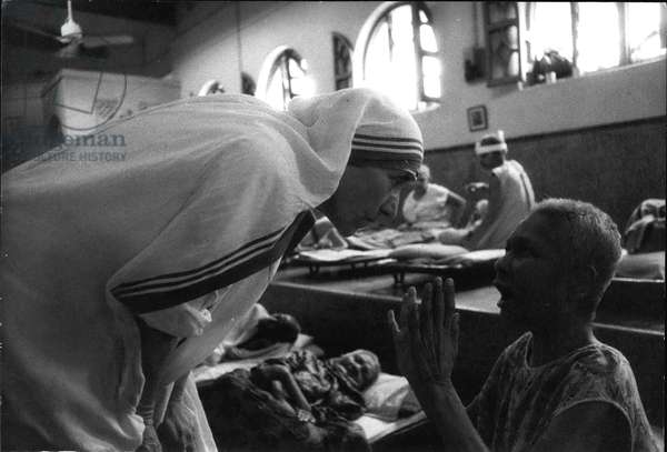 mother Teresa (Theresa) - Mother Teresa listens intently to the prayer of a dying victim of poverty