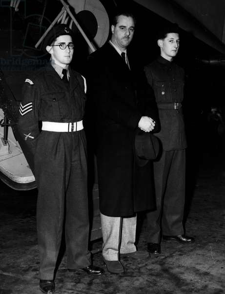 """Dec. 12, 1954 - Air Cadets Fly With The Under Secretary Of State For Air: When Mr. George Ward, M.P. Under secretary of State for Air left London Airport this morning for a tour of Royal Air Force unites in the Middle East, m two young cadets flew with him. Chosen From more than 40,000 Air Cadets in the United Kingdom, they will act as assistant air quartermasters in the Heating aircraft. They are, Cadet Harley Brian Hall, 17, of Bexley, Kent, and member of No. 1227 A.T.C. Squadron at Christchurch and Sidcup County Grammer School, who is hoping go tothe R.A.F. College at Cranwell, abnd Cadet Dan Villiers Dalap, 17, of """"Clan Connal"""". Manorway., Lee-on-Solent, Hants - a member of the Campbell College Combined Cadet Force, Norway Ireland, whose father is a former wing commander in the R.A.F. The 11,000 flight will take the boys over the Mediterranean to Cyprus and then on to Jordan Iraq, Bahrain and Trucial Okman state (Persian Gulf), Aden, Nairobi, Khartoum and the Canal Zone before retuning via Cyprus and Idris (Libya). It will last three week and is regarded as a special regard to the cadets for proficiency,;. Phot Shows Mr. George Ward, with the two Cadets, Cadet Dan Villiers Delap (left), and Cadet Harley Brian Hall (right), prior to departure"""