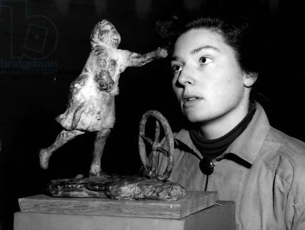 """Jan. 01, 1955 - Preparing For The"""" Young Contemporaries"""" Art Exhibition. """"Girl With Wheel ': Photo Shows Mis Jane Ross of Twickenham admires a sculpture by Ralph Brown of Highbury - with the name"""" Girl With Wheel"""" - seen during preparations at the R.B.A. Calories, Suffolk Street this morning for the"""" Young Contemporaries"""" exhibition which opens tomorrow"""