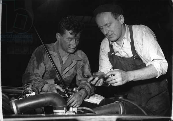 "Tue 03, 1954 - This Mechanic is Bourvil. Bourvil, the famous English screen and stage comedian, right, appears as a mechanic in the film"" Poisson D'Avril"" (April's Fool) now in the making in the Boulogne Billancourt Studio. Playing opposite him is the young actor Guy Loriquet"