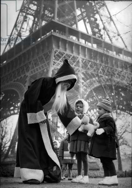 Pere Noel at the foot of the Eiffel Tower distributing gifts to children in Paris, France, December 22, 1960