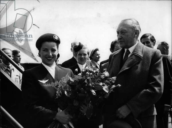 May 05, 1953 - Adenauer leaves Germany for Paris. Attend European Coal and Steel Board Conference.: Dr. Konrad Adenauer, the chancellor of the West German Federal Republic, is supposed to leave Germany to attend the European Coal Steel Conference. Before he boarded the plabe, 22-year-old Margot Wirges, a girl from Cologne, Adenauer's native-city, and Air France stewardess, presented the chancellor a big bouquet of Gloria-Dei-Roses, the chancellor's favorite flowers
