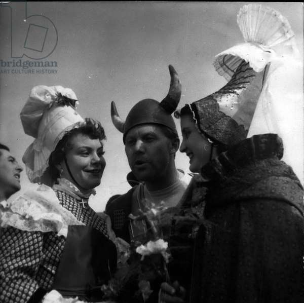 Apr. 12, 1954 - She Came From Normandy To Hear A Viking's Bugle: A Girl From Normandy In National Dress Smiles Cheerily As She Listens To A Viking Blowing His Horn. Picture Taken At The Kastrup Airfield, Copenhagen, On The Arrival Of The First Air France Viscount. A Group Of Girls From Normandy Got A Free Lift As Part Of The Ceremony